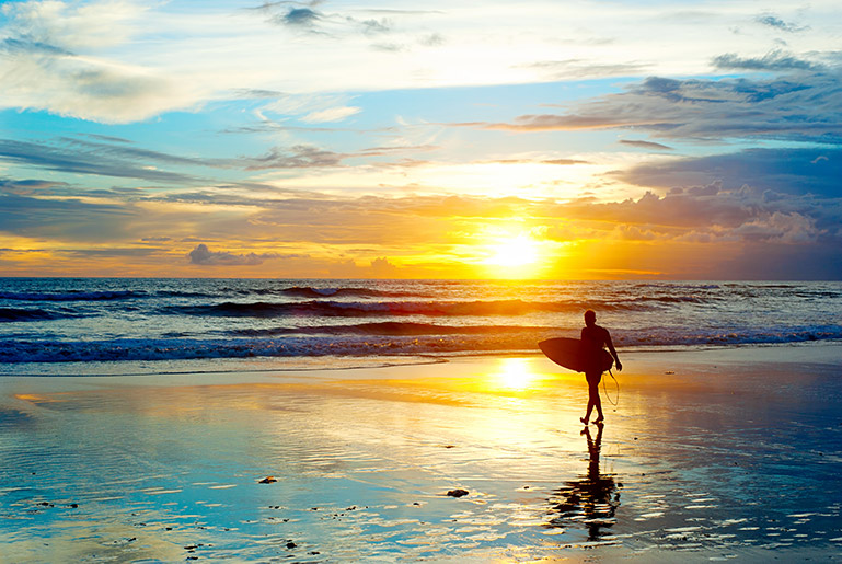 A surfer walks on the beach as the sun sets in Lombok, Indonesia.