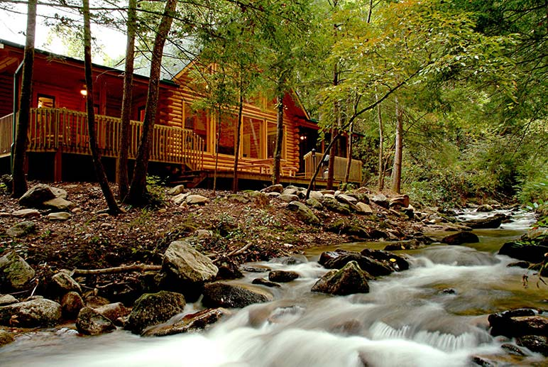 A wooded cabin and a stream in Rumbling Bald North Carolina lake resort.