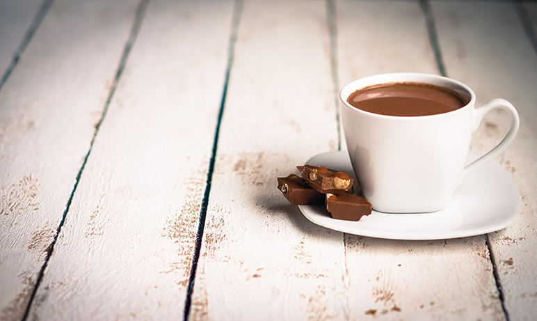 A cup of hot chocolate against wooden table.