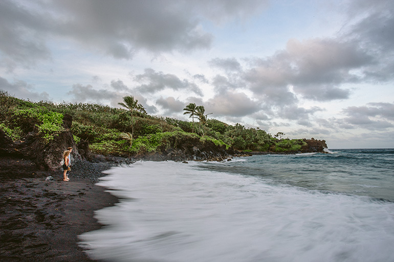 A man and a woman stand on the black sand beach in Maui, Hawaii, as the sun sets.