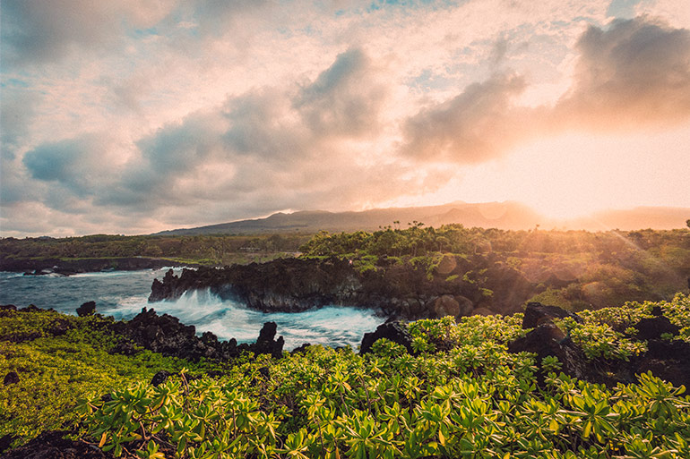 The sun sets over the horizon next to Black Sand Beach in Maui, Hawaii.