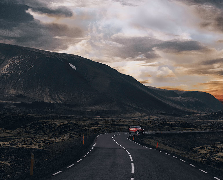 Car driving on a road in Iceland, renting a car in Iceland travel tips.